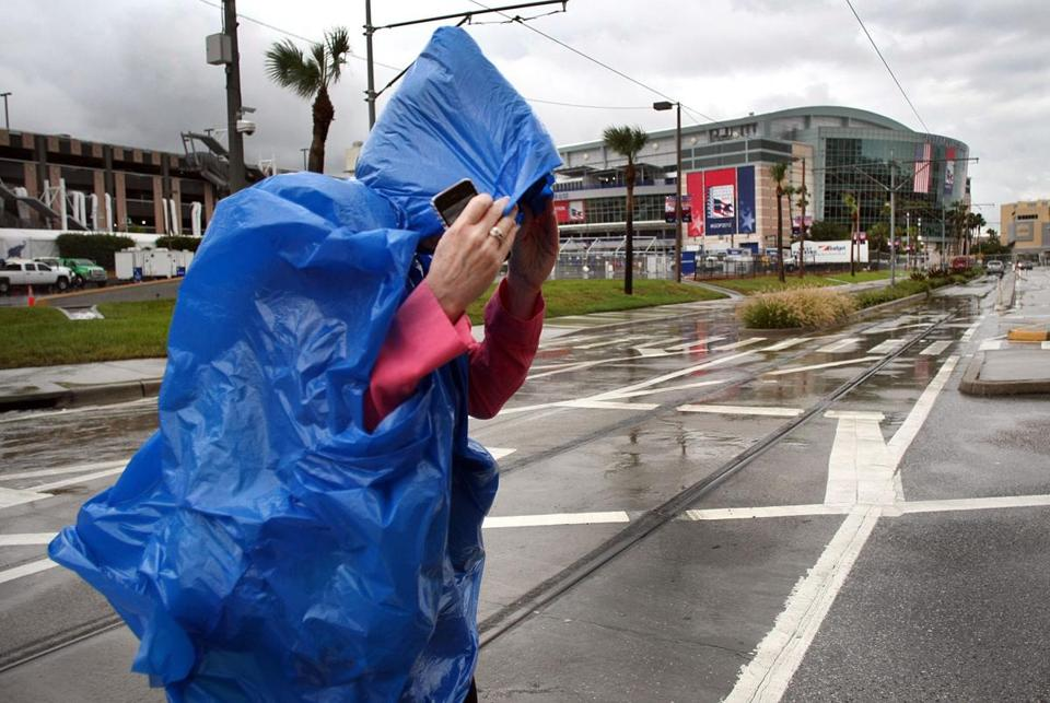 A convention worker covered up from the rain Monday as she walked near the site of the Republican gathering.