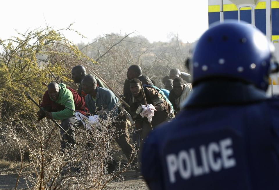 A policeman fired at protesting miners outside a South African mine in Rustenburg on Aug. 16.