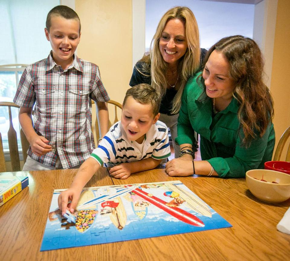 Drew Tardif, 10, worked on a puzzle with Mikalo Glennon, 7, and his mother Raquel Rohlfing.