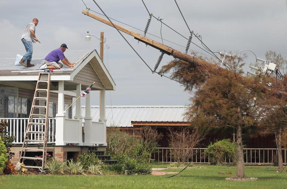 Workers repaired a roof next to a power pole destroyed by Hurricane Isaac in lower Plaquemines Parish in Boothville, La. Sunday was the first day some residents of lower Plaquemines were allowed to return to assess the damage.