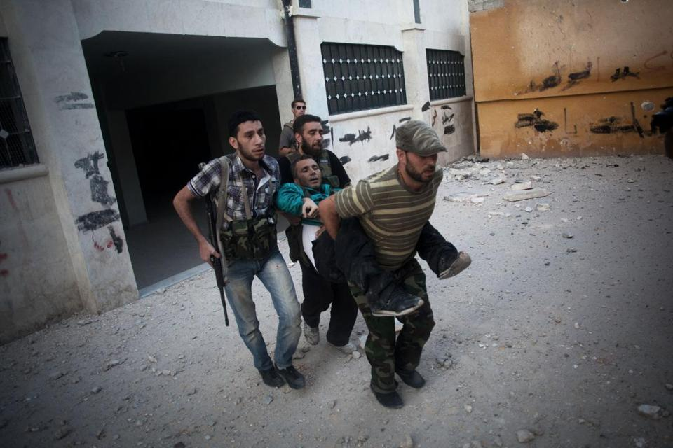 Free Syrian Army soldiers help a wounded fighter shot by a Syrian Army sniper in Aleppo, Syria, over the weekend.
