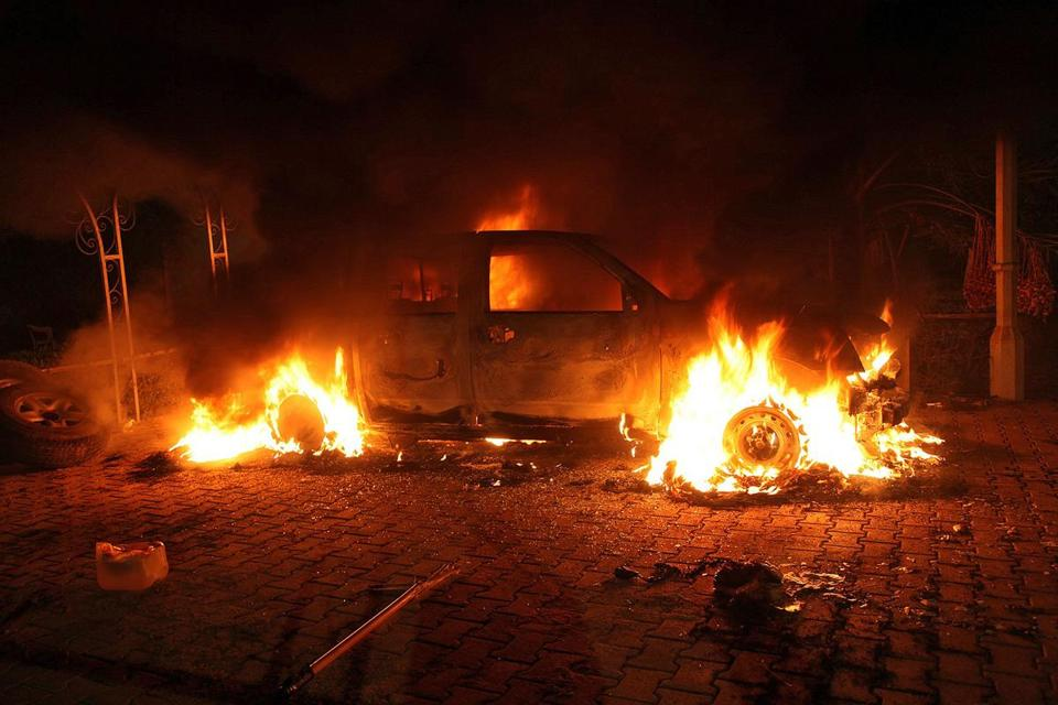 A vehicle and the surrounding area are engulfed in flames after it was set on fire inside the US consulate compound in Benghazi, Libya, late on Tuesday night.