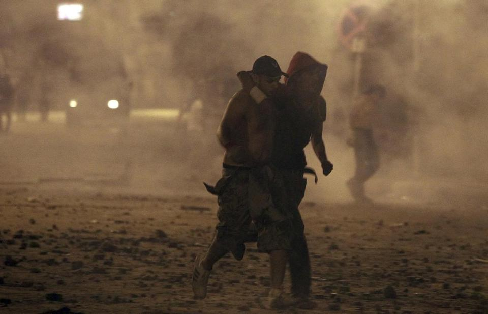 A protester helped an injured man near Tahrir Square in Cairo, Egypt.