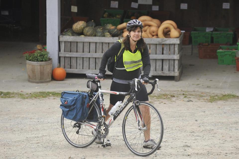 Susan Bacher lives in Carlisle and has pledged to grocery shop only by bike for one month. Here she shops at Hutchins Farm in Concord, then loads up the panniers on her bike for the ride home.