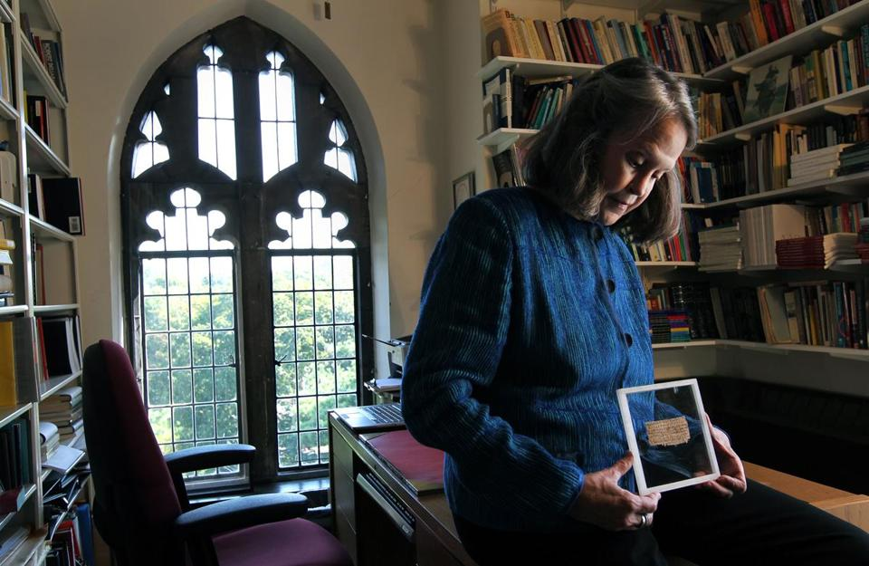 Karen L. King, Hollis Professor of Divinity at Harvard University, in her office with a papyrus fragment.
