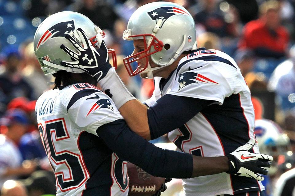 Quarterback Tom Brady and wide receiver Brandon Lloyd celebrated a fourth-quarter touchdown as the Patriots surged past the Bills, 52-28, at Buffalo on Sunday.