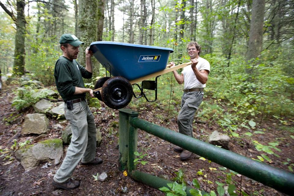Trustees of Reservations lifted their wheelbarrow, filled with construction supplies over the entry to the Noon Hill trail  in Medfield.