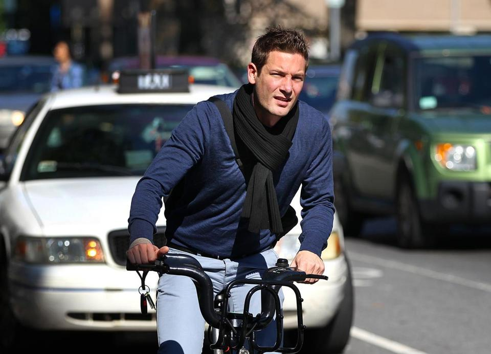 "Graduate student Jonas Naham, here riding a rented Hubway bike along Massachusetts Avenue, doesn't own a helmet. ""If I had one, it wouldn't be where my bike was,'' he says."
