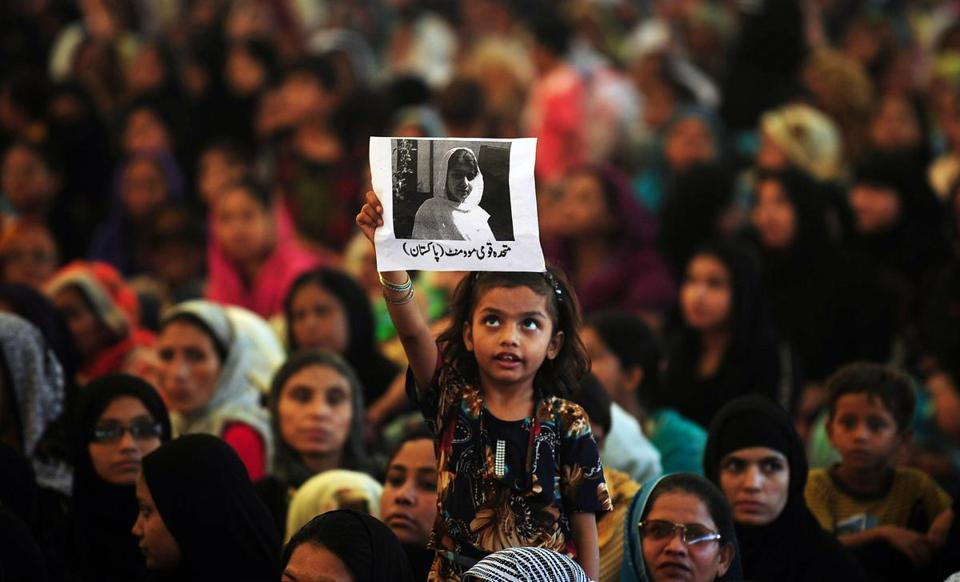 A Pakistani girl held up a photograph of Malala Yousafzai during a vigil Wednesday in Karachi.