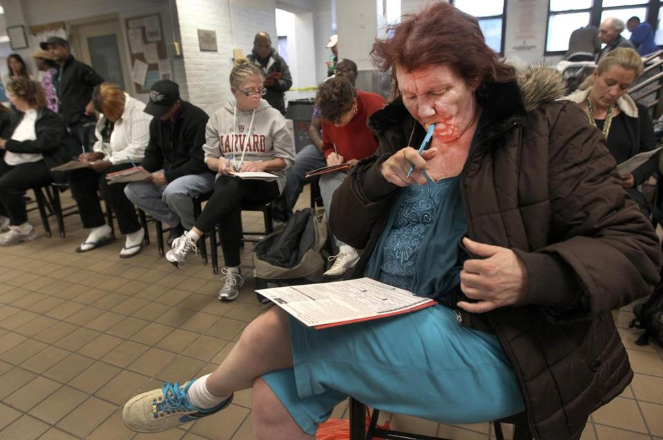 Mary Hutchinson and other residents of the Pine Street Inn filed in voter registration forms Thursday at the shelter.