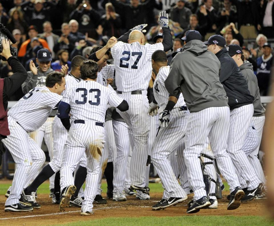 Raul Ibanez (27) celebrated with teammates as he reached home plate after hitting the game-winning home run in the 12th inning.