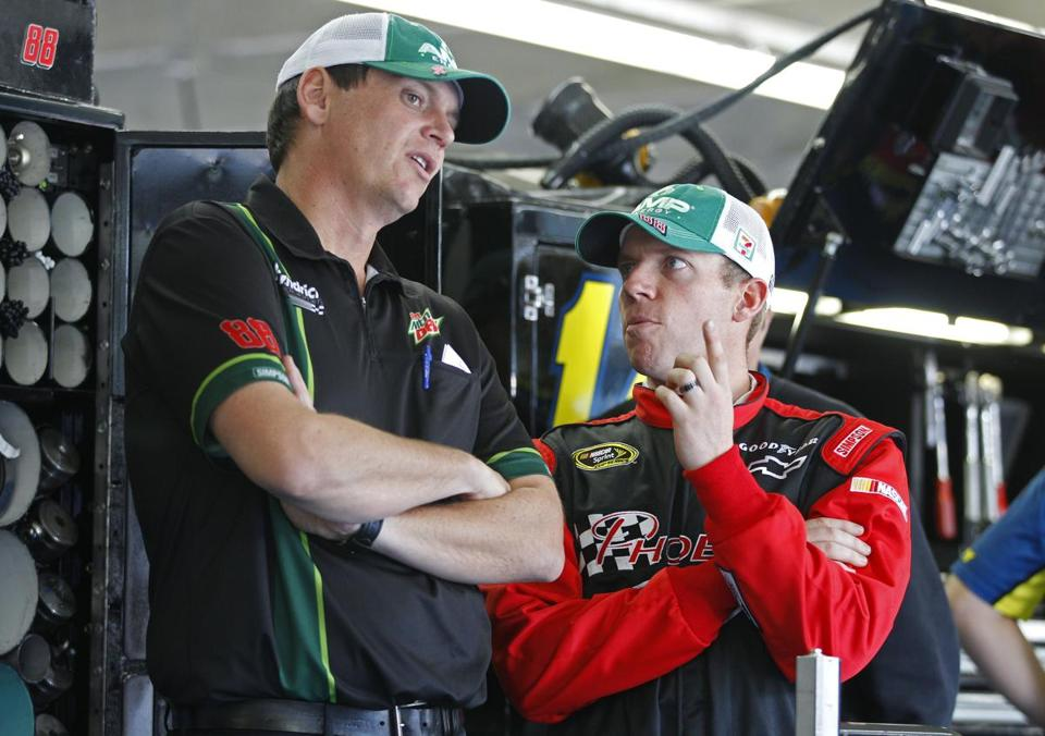 Regan Smith (right), Dale Earnhardt Jr.'s replacement, talks with crew chief Steve Letarte (left) before practice.
