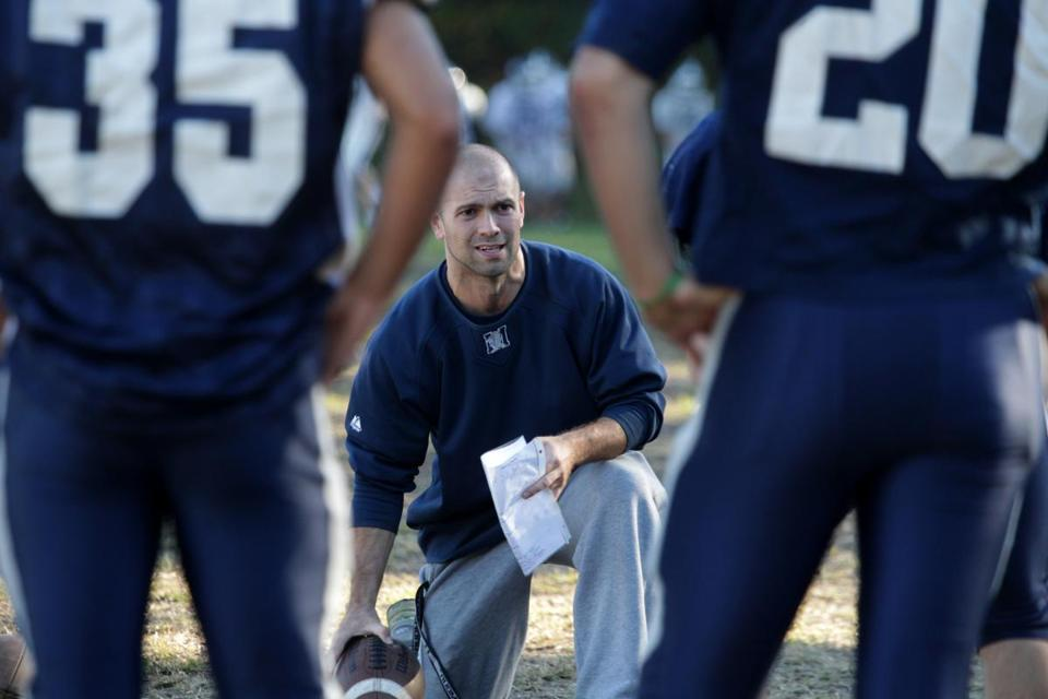Jason Nascimento (kneeling) was named interim head football coach at Medford High after Rico Dello Iacono was let go earlier this season.