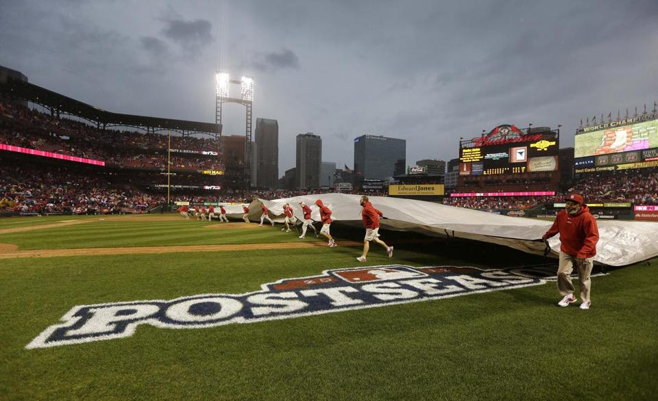 There was rain, rain everywhere. In St. Louis (above), the crew covered the field during a delay. In Detroit, the game didn't even get started.