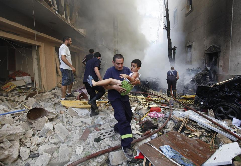 A rescue worker carried an injured boy at the scene of an explosion in the Beirut Christian neighborhood of Achrafiyeh.