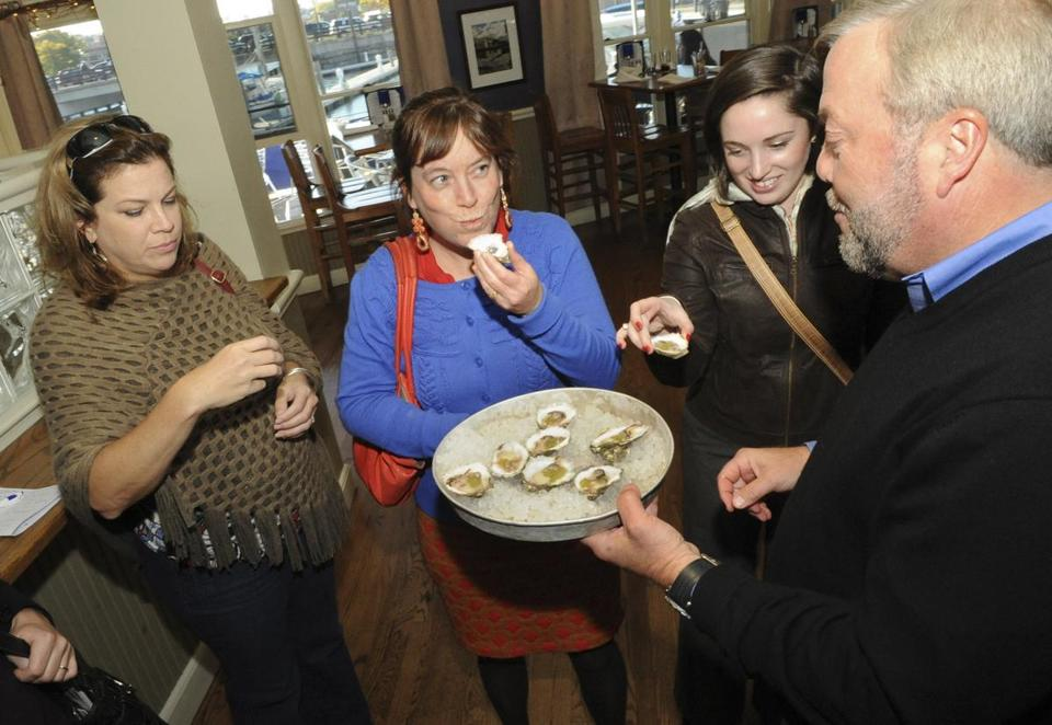 George Carey, founder of Finz Seafood & Grill, serves raw oysters to (from left) Charlene Peters, Heather Cathcart, and Jen DiSciullo.