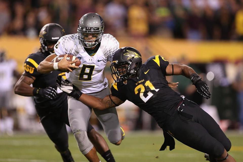 Oregon quarterback Marcus Mariota tries to work his way past Arizona State's Chris Young (21) in the Ducks' 43-21 win.