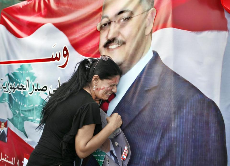 A woman in Lebanon mourned at a poster of senior intelligence official Wissam al-Hassan, who died in a car bombing Friday in Beirut. Protests rocked the city on Saturday.