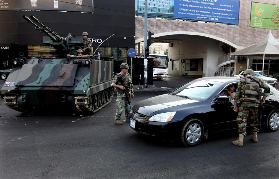 Soldiers checked a car in Tripoli, Lebanon, Monday during clashes between supporters and opponents of the Syrian regime.