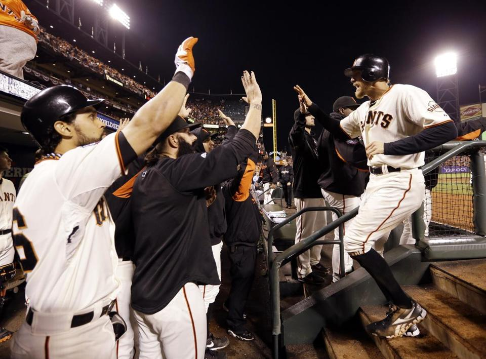 The Giants' Hunter Pence is congratulated after scoring during the seventh inning.