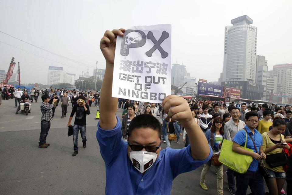 A demonstrator held up a flier opposing plans to expand a petrochemical factory in the city of Zhejiang on Sunday