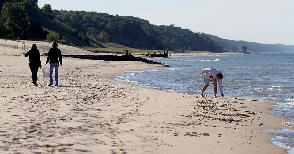 A man picked up a piece of litter along the shoreline at Pere Marquette beach in Muskegon, Mich., in September as part of the Alliance for the Great Lakes annual cleanup effort.