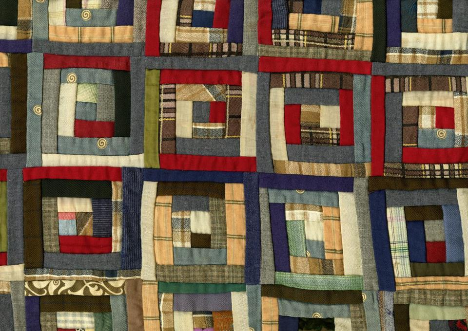 Detail from a circa 1865 quilt, made by an Illinois woman from uniforms worn by her sons on opposite sides in the Civil War, in an American Textile History Museum display.