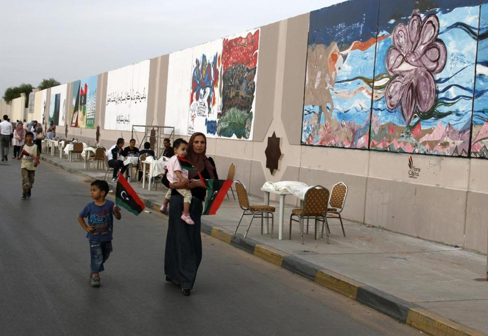 Murals in Tripoli celebrate the one-year anniversary of Moammar Khadafy's fall. Libya is trying to redistribute power.