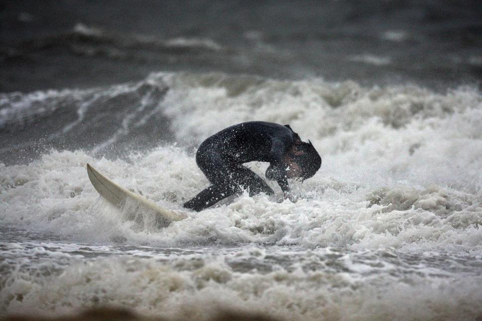 Tyler Buck, a student at UMass-Dartmouth School of Law, takes to the waves off Wollaston Beach in Quincy.