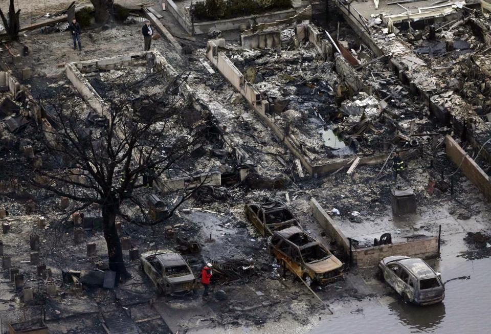 Houses were destroyed by a fire in the Breezy Point section of Queens, N.Y. Estimates of total damage have been raised.