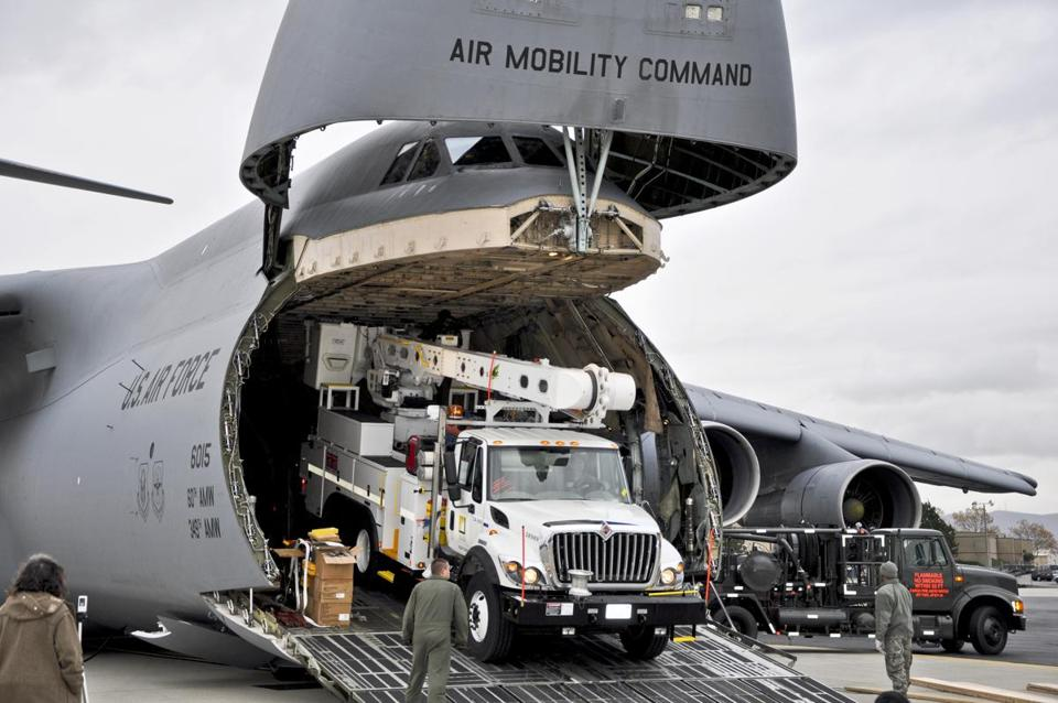 US Air Force crews in New York offload power grid repair equipment from Southern California Thursday. The Defense Department initiated the airlift operation.