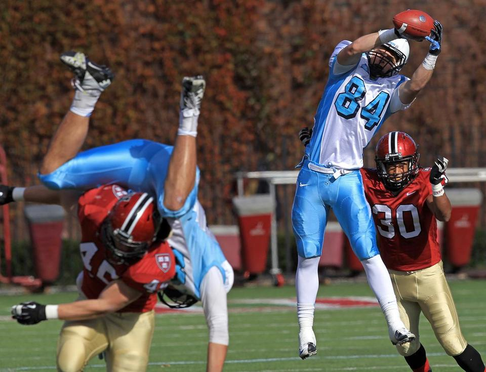 Columbia's Connor Nelligan makes the catch but is about to get hit hard by Harvard's Jaron Wilson — much like his teammate close by.