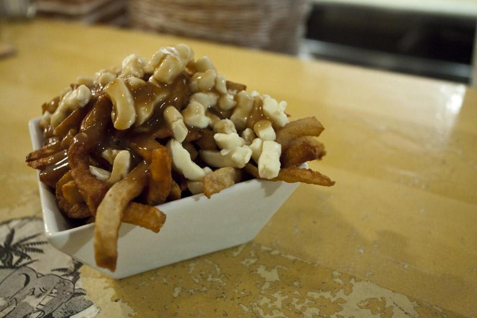 Poutine is a signature dish that originated in Quebec, and is a serving of french fries topped with cheese curds and gravy.