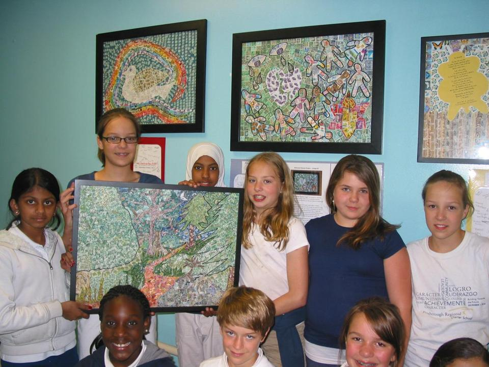 Students from Foxborough Regional Charter School this past June, with one of the collages made out of stamps.