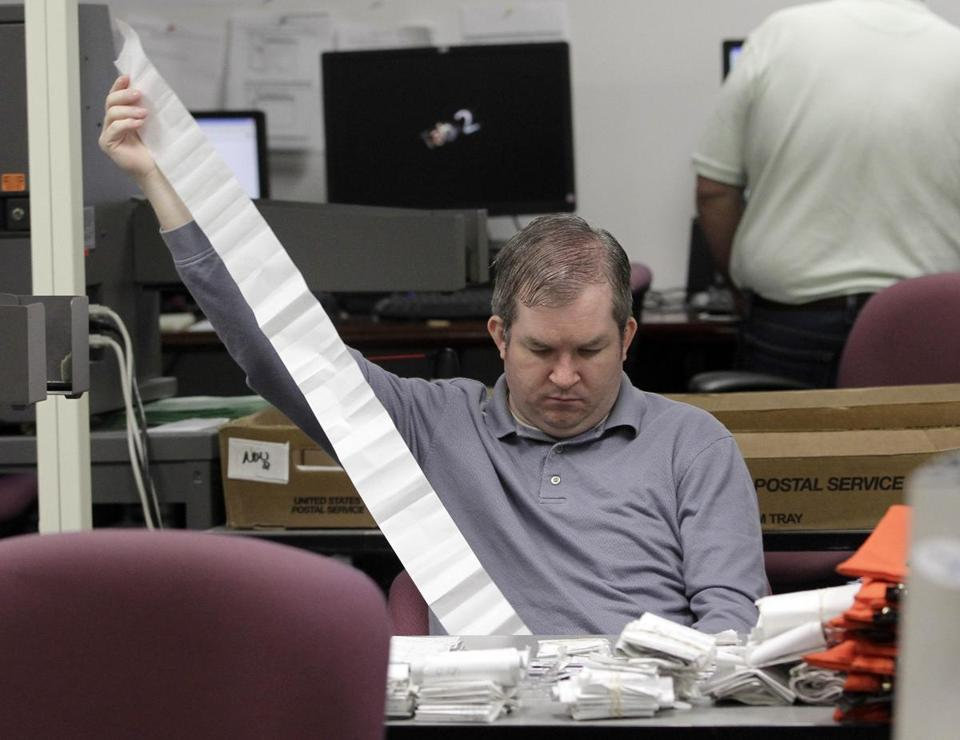 An employee tallied absentee ballot reports in Doral, Fla., on Thursday.