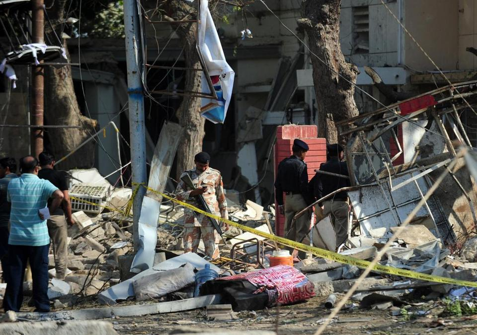 Pakistani security officials surveyed wreckage at the scene of a suicide bomb attack on a Ranger complex in Karachi on Thursday. The blast killed three and injured at least 20.