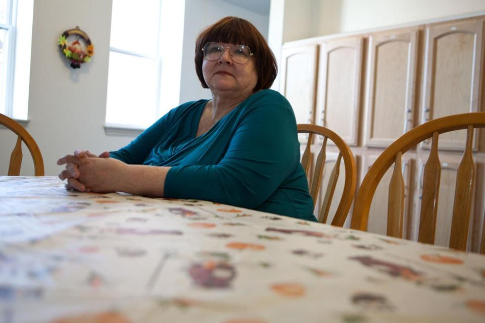 Diana Dinapoli sits at the table in the shared kitchen of her apartment building in Salem, where she will cook a holiday meal.