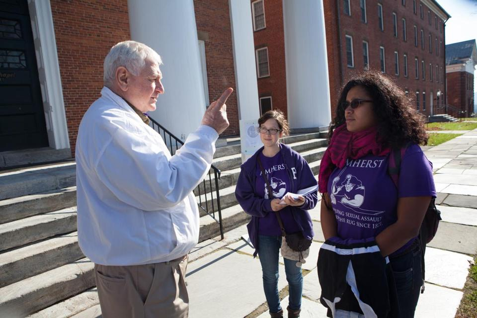 Peter Sokaris, an Amherst College alumnus, spoke to students Ivonne Ortega and Isabelle D'Arcy, who were wearing shirts bearing a message critical of the school's response to recent sexual assaults.
