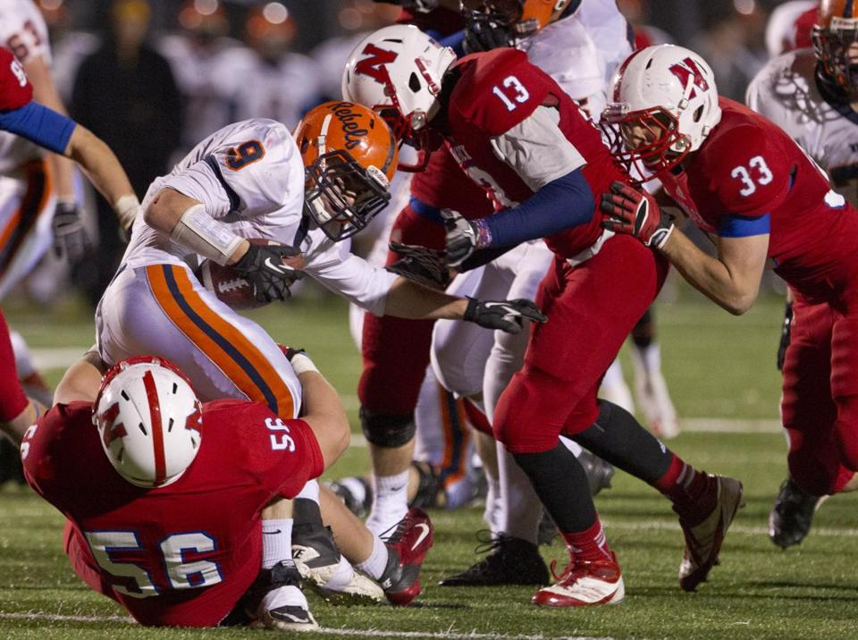 Walpole's Connor Moriarty is stopped in his tracks by Natick defenders Robby Beausoleil (56) and Trenton Wright (13).