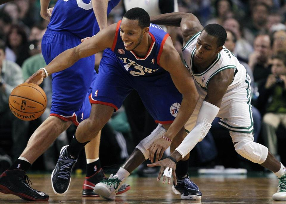 Philadelphia 76ers' Evan Turner and Boston Celtics' Rajon Rondo, right, scramble for a loose ball in the second quarter on Friday.