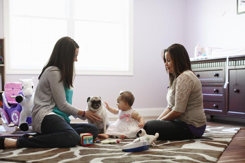 Ten-month-old Amara plays at home in Billerica with mom Kate Mazzola and her surrogate, Courtneylee Martinez.