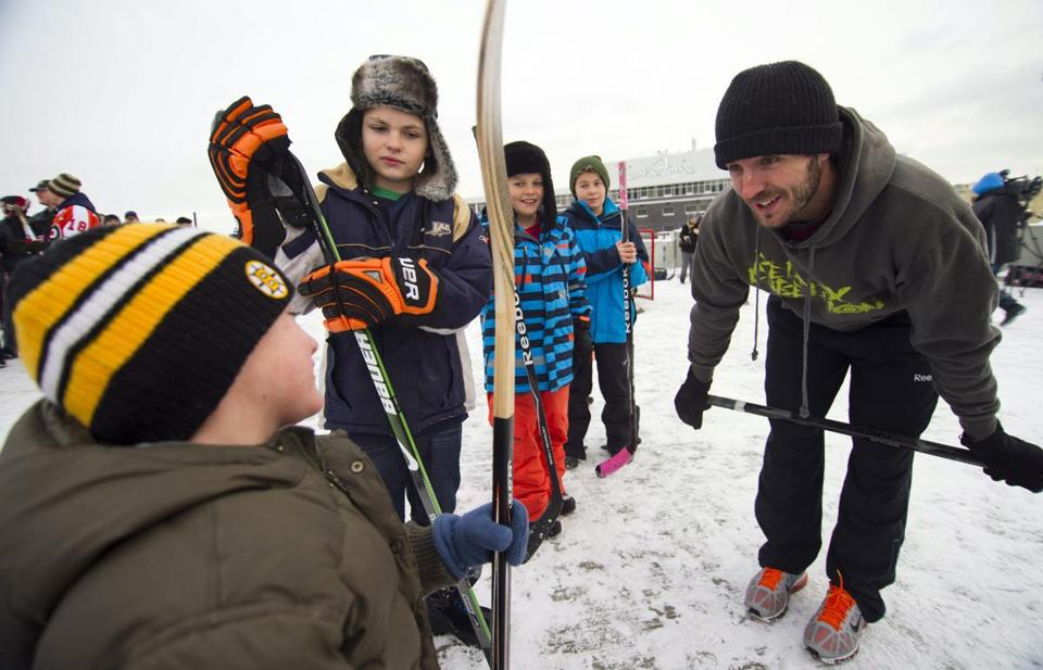 Los Angeles Kings star Mike Richards gets together with some young fans to play street hockey Tuesday atop a parking garage in Winnipeg.