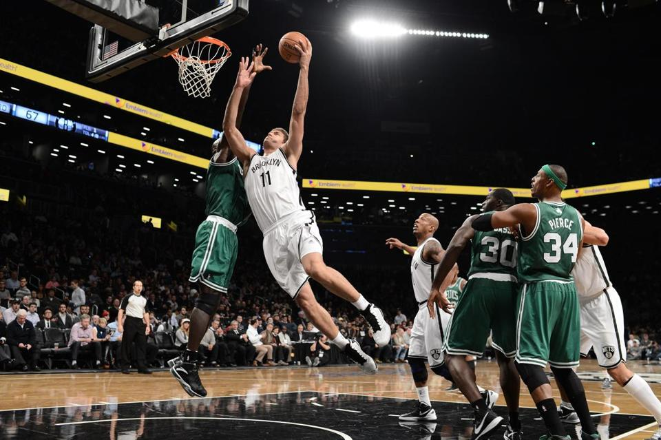 Brooklyn Nets center Brook Lopez goes to the basket as Boston Celtics power forward Kevin Garnett defends during Thursday's game.
