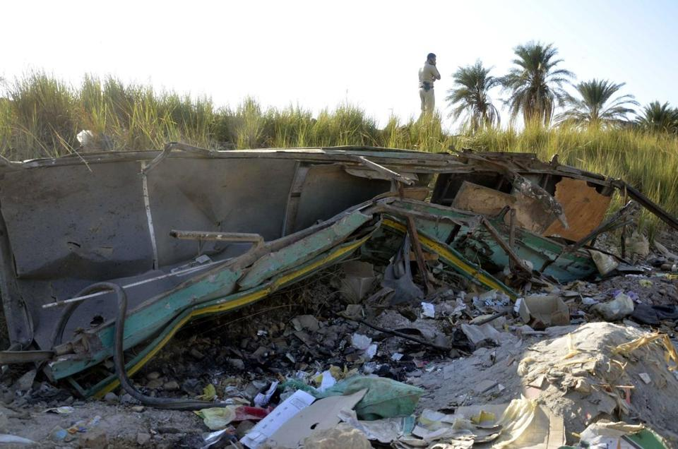 A man stood at the site where a train struck a bus Saturday, near al-Mandara village in Assiut Province, Egypt.