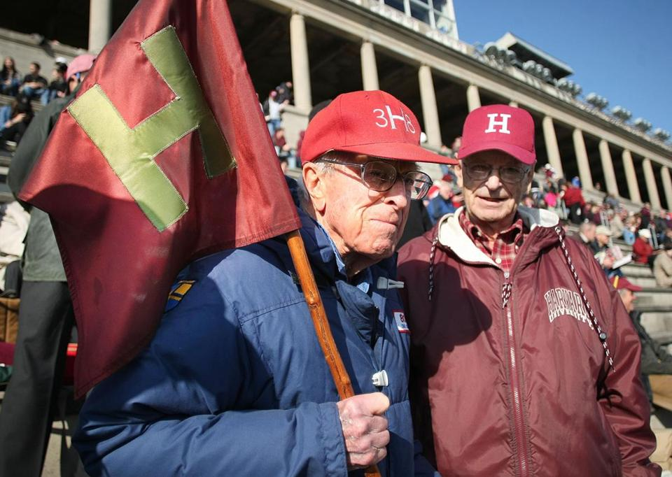 Paul Lee, Harvard class of '46, (right) passed the modern Little Red Flag to Dick Bennink, class of '38, at the Harvard-Yale football game on Saturday.