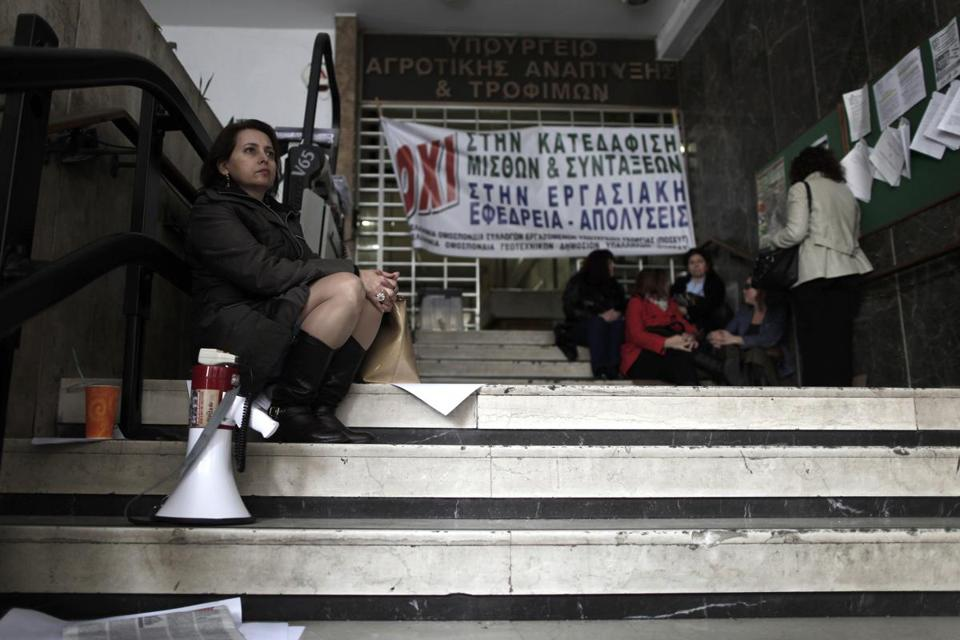 "Agriculture ministry workers were seen at the entrance to the ministry headquarters in Athens, which was occupied by protesting employees on Monday. The banner reads ""No to the demolition of salaries and pensions."""