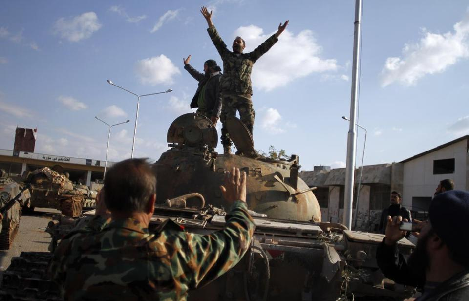 Syrian fighters celebrated their victory atop a tank after storming a military base in Aleppo on Monday.