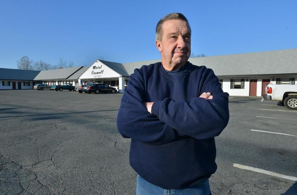 Russell H. Caswell, outside his family's motel on Main Street in Tewksbury, is awaiting a ruling on his legal battle with the US government.