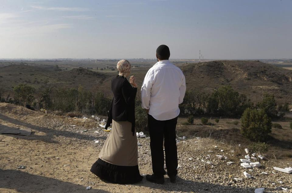 An Israeli couple watched the Gaza Strip in the background as they stood on a hill at the Israeli town of Sderot on Tuesday.