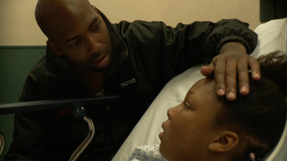 "Demia Bruce comforts daughter Deja in a scene from the documentary ""The Waiting Room"""